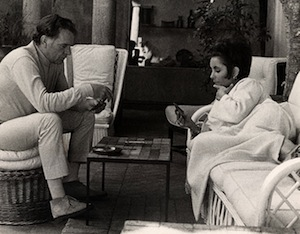 ca. 1967, St.-Jean Cap Ferrat, France --- Actors Richard Burton (wearing white turtleneck and slacks) and Elizabeth Taylor (wearing caftan from Givenchy boutique), seated and lounging and playing gin while on vacation at La Fiorentina, Saint-Jean-Cap-Ferrat. --- Image by © CondÈ Nast Archive/CORBIS