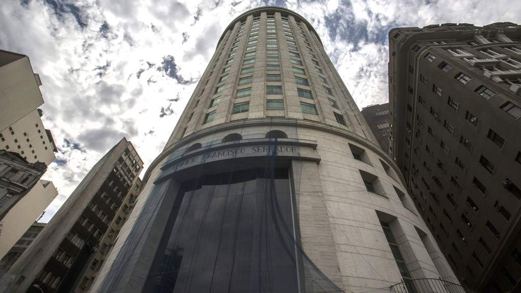 The 23-story Serrador building hangs a plastic tarp to protect its glasses against vandalism in Rio de Janeiro , Wednesday, Sep 9, 2015. At opposite ends of downtown Rio de Janeiro, projects tied to Donald Trump and Eike Batista -- one a billionaire-turned-politician, the other an ex-billionaire -- have come to represent the city's real-estate bust. The Serrador building, a granite-and-glass art deco tower near Rio's local airport, has sat empty since Batista's failed empire of commodities companies abandoned it last year. Four miles away, in the city's gritty port district, an ambitious office project that Trump lent his name to is still nothing more than a weed-filled lot about one year after construction was slated to begin.(Bloomberg Photo/Dado Galdieri)
