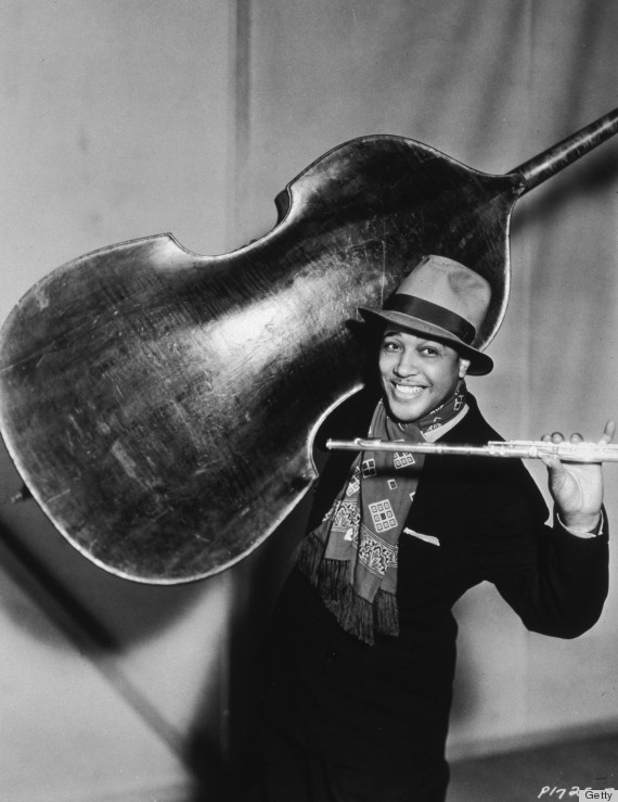 1934: American jazz pianist, composer and bandleader Duke Ellington (1899 - 1974) smiles as he holds a double bass on his shoulder and a flute in one hand, Hollywood, CA. He is wearing a fedora, a suit, and a scarf around his neck. Ellington and his band were in Hollywood to appear in director Mitchell Liesen's film, 'Murder at the Vanities.' (Photo by Frank Driggs/Frank Driggs Collection/Getty Images)