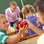 Portrait of schoolgirl passing red apple to classmate during lesson